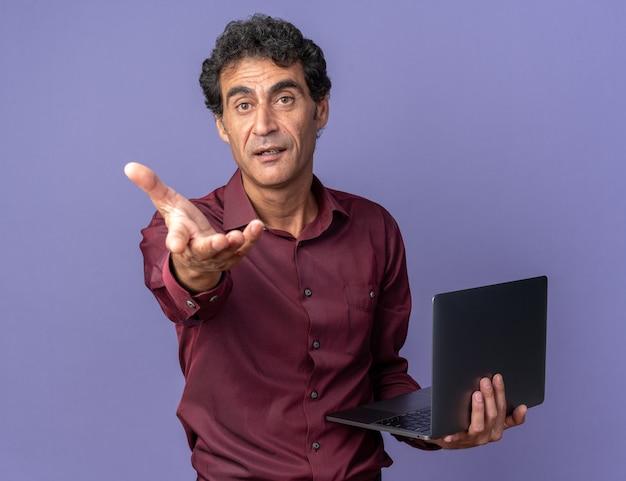 Senior man in paars shirt met laptop die naar de camera kijkt en een gebaar maakt