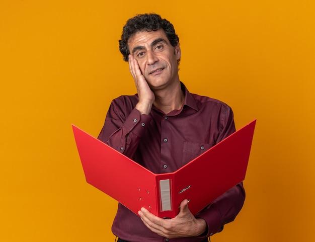 Senior man in paars shirt met map kijkend naar camera glimlachend