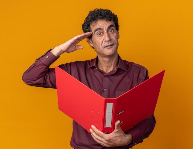 Senior man in paars shirt met map kijkend naar camera met blij gezicht groetend