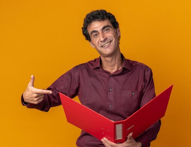 Senior man in paars shirt met map wijzend met wijsvinger ernaar glimlachend zelfverzekerd kijkend naar camera die over oranje staat