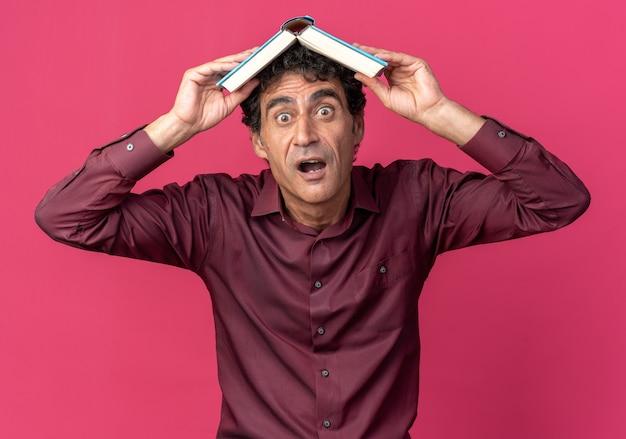 Senior man in paars shirt met open boek boven zijn hoofd en kijkt verbaasd en verbaasd over roze achtergrond