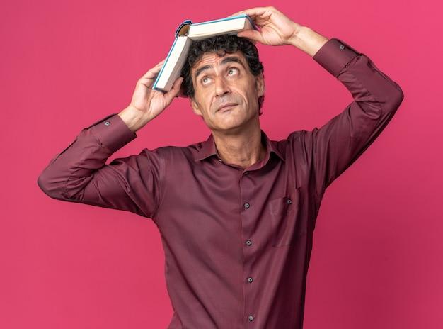 Senior man in paars shirt met open boek boven zijn hoofd en ziet er moe en verveeld uit terwijl hij over roze staat