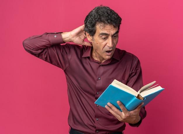 Senior man in paars shirt met open boeklezing die verbaasd en verrast kijkt