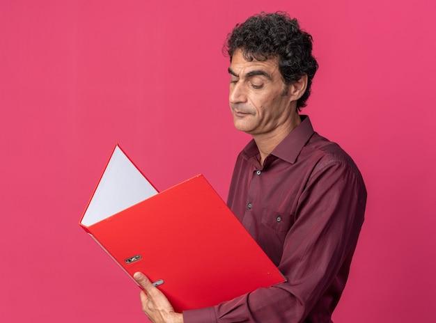 Senior man in paars shirt met open map die ernaar kijkt met een serieus gezicht