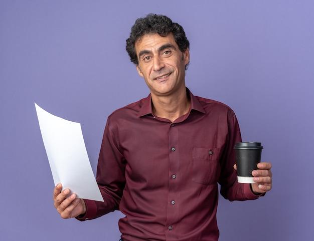 Senior man in paars shirt met papieren beker en blanco pagina die naar de camera kijkt met een glimlach op het gezicht over een blauwe achtergrond
