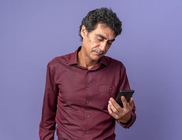 Senior man in paars shirt met smartphone die ernaar kijkt met een serieus gezicht over blauw