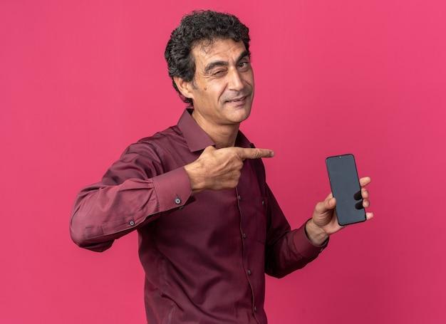 Senior man in paars shirt met smartphone wijzend met wijsvinger ernaar glimlachend en knipogend over roze