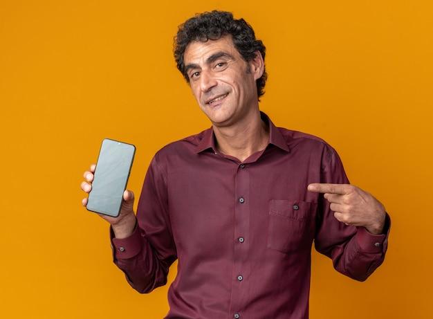 Senior man in paars shirt met smartphone wijzend met wijsvinger erop glimlachend zelfverzekerd kijkend naar camera staande over oranje achtergrond