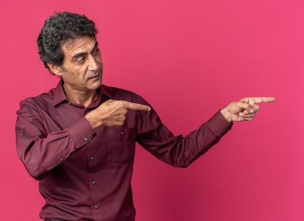 Senior man in paars shirt opzij kijkend met een serieus gezicht wijzend met wijsvingers naar de zijkant staande over roze achtergrond
