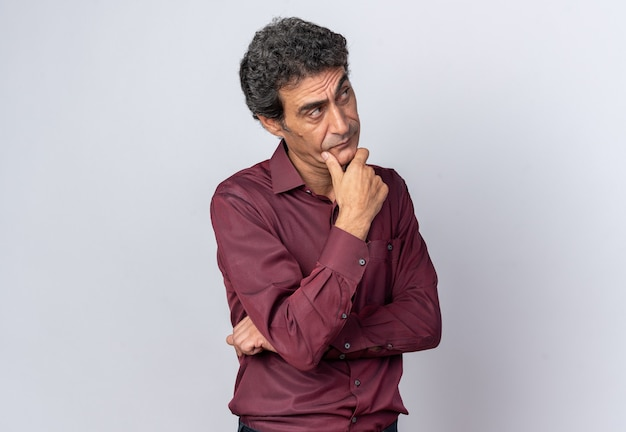 Senior man in paars shirt opzoeken verbaasd denken staande over witte achtergrond