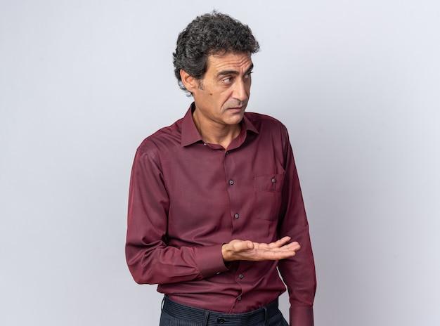 Senior man in paars shirt ziet er verward uit en steekt zijn arm op in ongenoegen en verontwaardiging