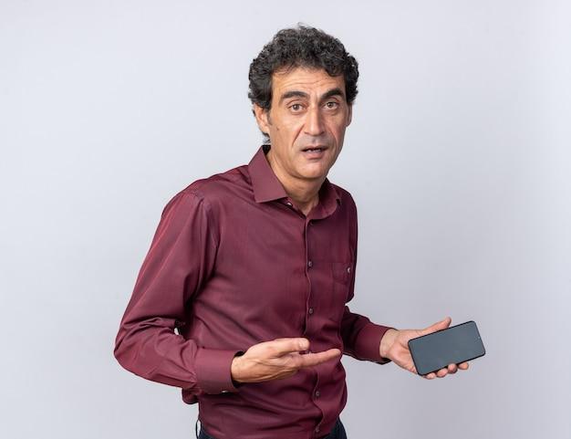 Senior man in paars shirt ziet er verward uit terwijl hij een smartphone vasthoudt die over wit staat