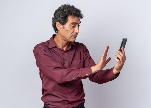 Senior man in paars shirt ziet er verward uit terwijl hij smartphone vasthoudt en verdedigingsgebaar maakt