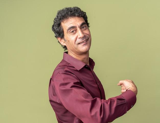 Senior man in paars shirt ziet er zelfverzekerd uit en wijst naar achteren terwijl hij over groen staat