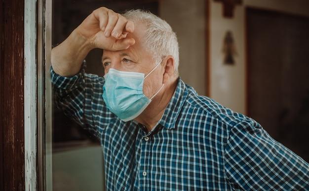 Senior man in quarantaine geplaatst door coronavirus, covid-2019 bij een huis, naar buiten kijkend bij de windown