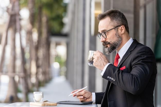 Senior man in slimme pak denken en zitten in de koffietafel buiten.