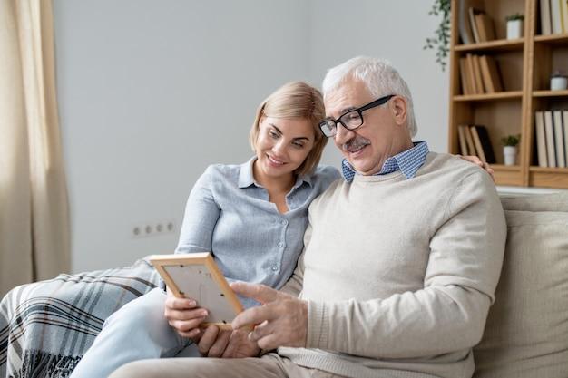 Senior man in vrijetijdskleding toont zijn foto van zijn gelukkige jonge dochter in frame terwijl hij het thuis met haar bespreekt