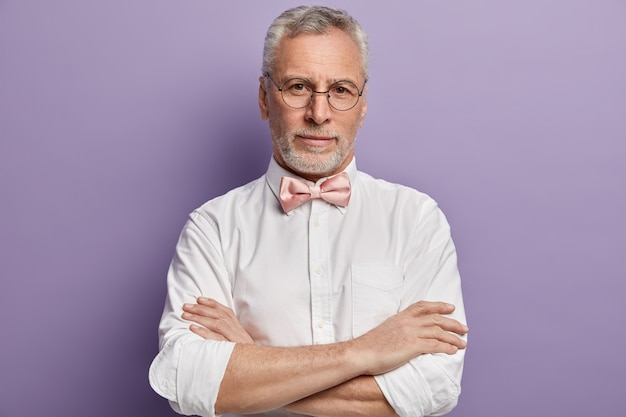 Senior man in wit overhemd en roze bowtie