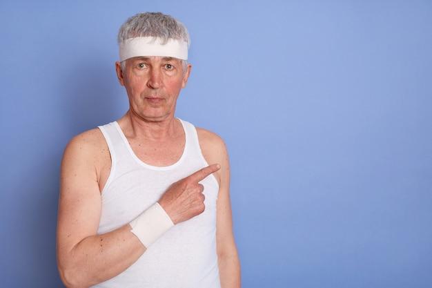 Senior man in wit t-shirt kijken en opzij wijzend met zijn wijsvinger