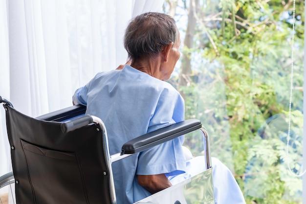Senior man in zijn rolstoel met zijn rug in het ziekenhuis.