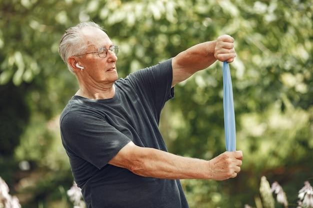Senior man in zomer park. grangfather gebruikt een eraiser.