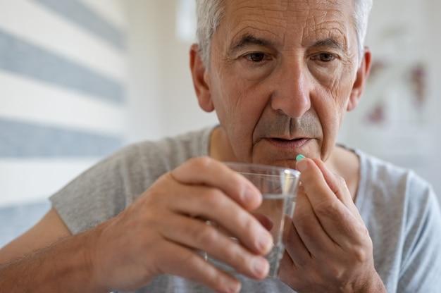 Senior man innemen van medicijnen