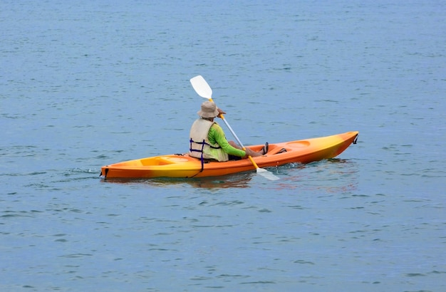 Senior man kanoën op het strand bij zonsondergang