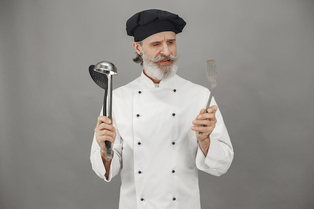 Senior man kiest pollepels. chef-kok in een zwarte pet in zijn hoofd. professionele benadering van zaken.