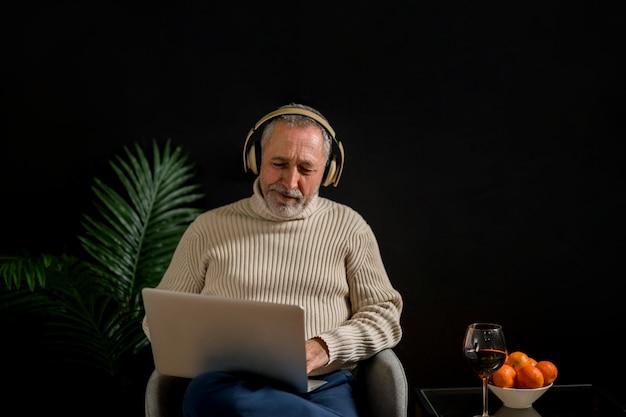 Senior man kijken naar film in de buurt van mandarijnen en wijn