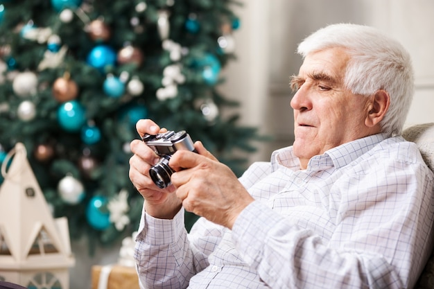 Senior man kijken naar retro-stijl camera