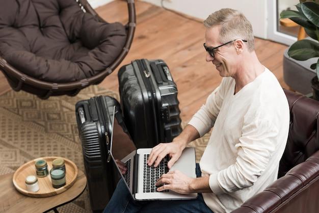 Senior man kijkt door zijn laptop