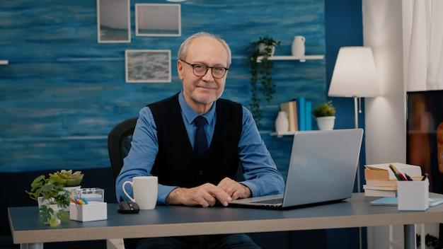Senior man kijkt naar camera glimlachend zittend op de werkplek aan een bureau dat vanuit huis werkt terwijl de oude vrouw tv kijkt op de achtergrond. gepensioneerde zakenman voorbereid op online vergadering met moderne gadgets