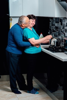 Senior man knuffelt met liefde zijn tedere vrouw kookt samen thuis eten de liefhebbende echtgenoot kuste...