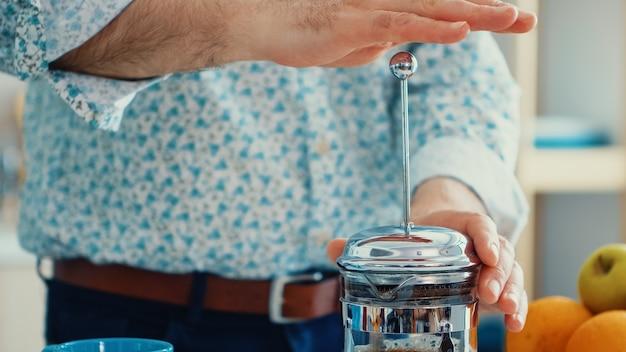Senior man koffie bereiden met behulp van franse pers in de keuken voor het ontbijt. bejaarde in de ochtend genietend van vers bruin café espressokopje cafeïne uit vintage mok, filter ontspannen verfrissing
