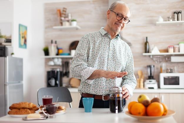 Senior man koffie maken met behulp van franse pers tijdens het ontbijt in de keuken. bejaarde in de ochtend genietend van vers bruin café espressokopje cafeïne uit vintage mok, filter ontspannen verfrissing