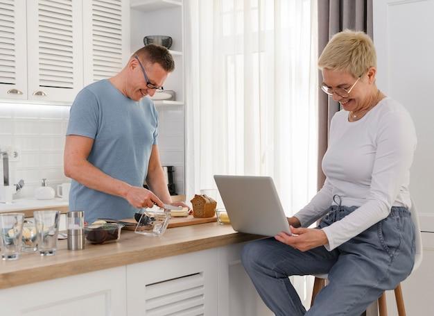 Senior man koken ontbijt voor zijn vrouw gelukkige paar thuis