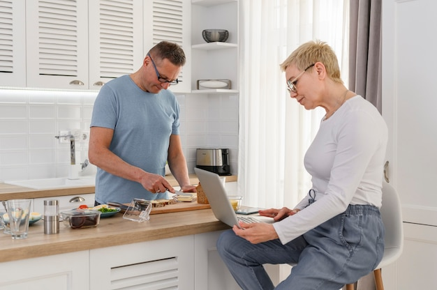 Senior man kookt ontbijt voor zijn vrouw terwijl ze videobellen naar familieleden op laptop gelukkig
