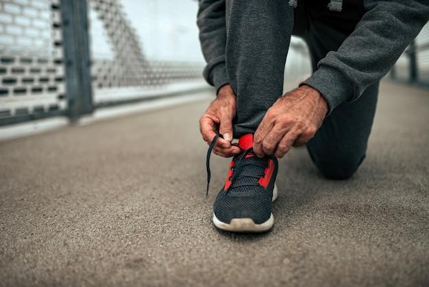 Senior man koppelverkoop schoenveters vóór een run. detailopname.