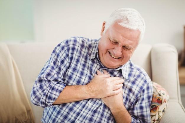 Senior man krijgt pijn op de borst in de woonkamer