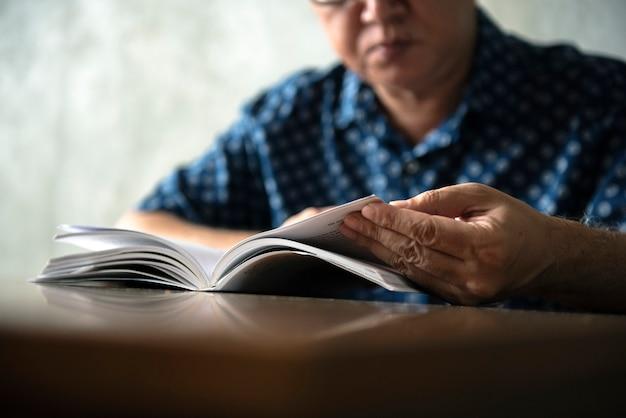 Senior man leesboek thuis