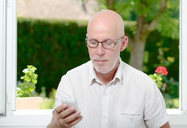 Senior man leest bericht op smartphone