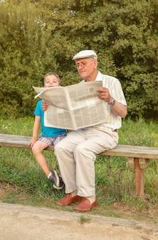 Senior man leest en verveeld schattig kind kijkt uit over de krant zittend op een bankje. twee verschillende generaties concept.