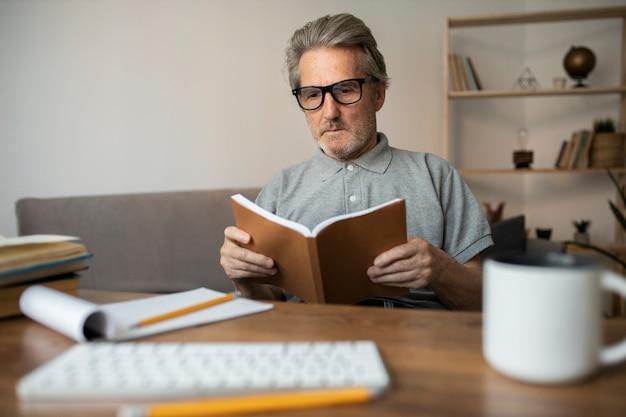Senior man leest zijn les voor school