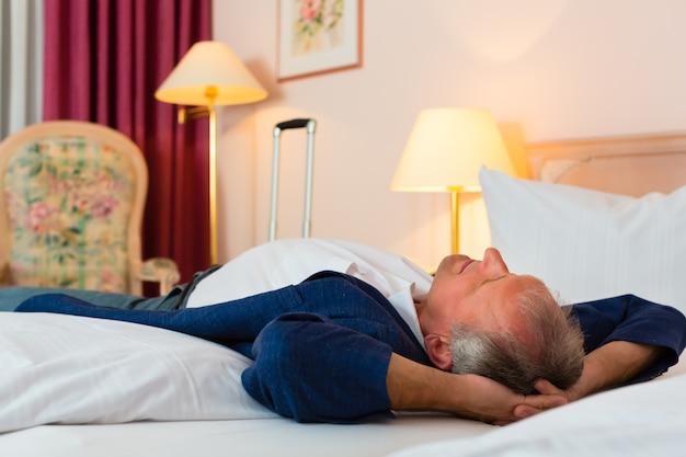 Senior man liggend op het bed in de hotelkamer