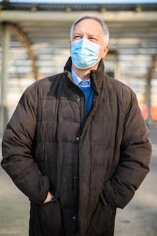 Senior man loopt buiten en draagt een beschermend masker tegen coronavirus pandemie