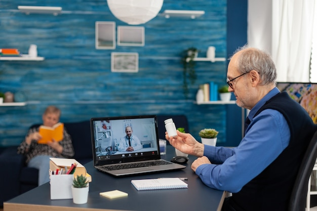 Senior man luisteren arts tijdens videoconferentie