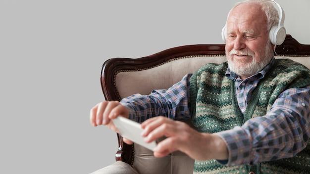 Senior man luisteren muziek op mobiel