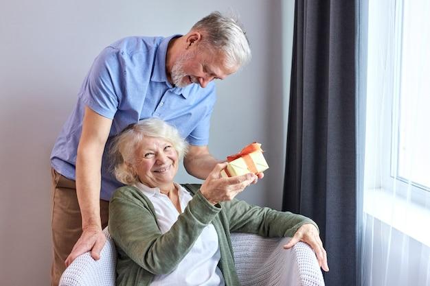 Senior man maakt verrassing geschenkdoos geven aan aardige mooie vrouw, gelukkige oude vrouw krijgt onverwacht cadeau van echtgenoot die een romantisch weekend doorbrengt of samen een jubileum viert thuis