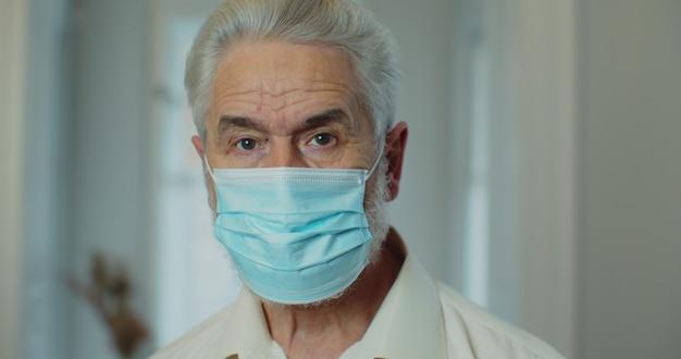 Senior man medische masker op gezicht zetten zelfisolatie thuis. portret van een senior man met een medisch masker, in quarantainemodus.