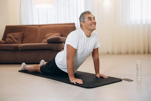 Senior man mediteert terwijl hij cobra pose doet in de woonkamer